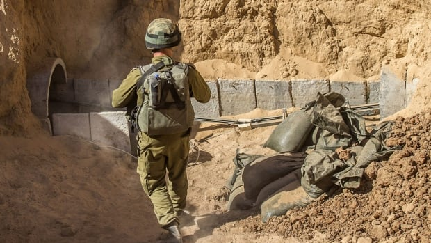 An Israeli army officer walks near the entrance of a tunnel at the Israel-Gaza border on July 25, 2014. The tunnel was allegedly being used by Palestinian militants for cross-border attacks.