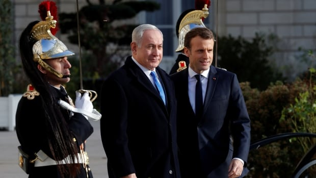 French President Emmanuel Macron, right, welcomes Israeli Prime Minister Benjamin Netanyahu for a meeting focusing on bilateral ties, Iran, the Middle East peace process and other regional crises at the Elysée Palace in Paris on Sunday.