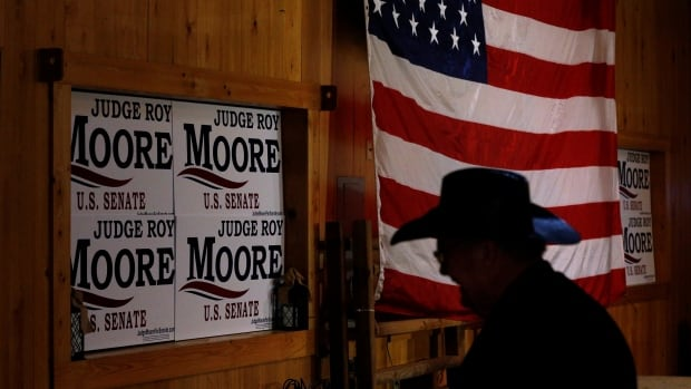 A supporter of Republican candidate for U.S. Senate Roy Moore walks past an American flag before a campaign rally in Fairhope, Ala., earlier this month. Republican fixers missed all the warning signs coming out of Alabama and ended up with the highly controversial Moore on the ballot.