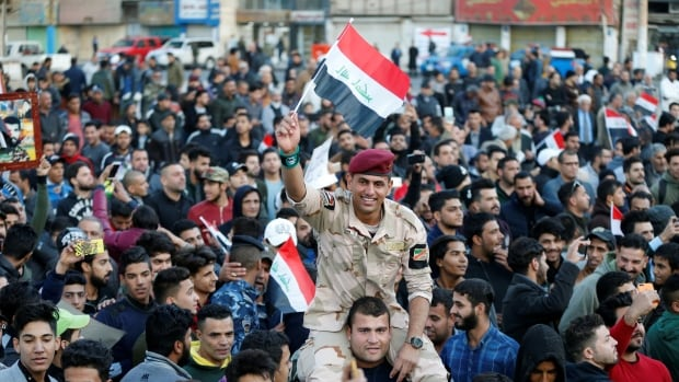 A member of Iraq's security forces carries an Iraqi flag as he celebrates the official victory over the Islamic State at Tahrir Square in Baghdad on Sunday.