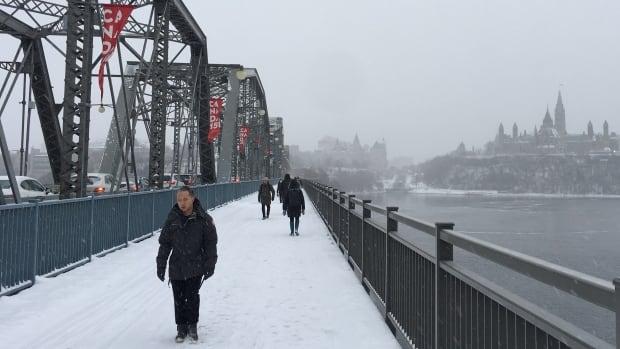 Pedestrians cross the Alexandra Bridge over the Ottawa River during a winter storm Tuesday, Dec. 12, 2017.
