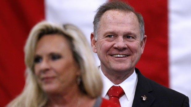Roy Moore, the Republican candidate in Alabama's special election for the U.S. senate, smiles while his wife  Kayla delivers remarks during a campaign rally Monday night. Moore denies allegations that he was once a sexual predator.