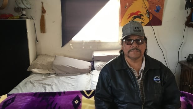 Glenn Moosomin sits in an unheated porch which is being used as a bedroom by people on the Mosquito, Grizzly Bear's Head, Lean Man First Nation.