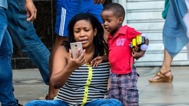 In this Jan. 6 photo, a woman with her child uses a public wifi hotspot in Havana, Cuba. A new report from UNICEF found that women and children in the developing world lack critical access to the internet and the opportunities it holds.