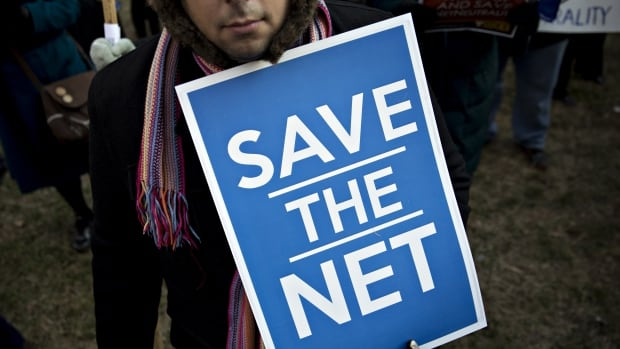 A demonstrator opposed to the roll back of net neutrality rules holds a 'Save The Net' sign outside the Federal Communications Commission headquarters in Washington, D.C., on Thursday.