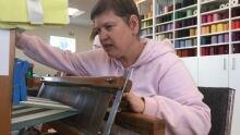 Brenda Henshaw works the loom in the weaving room.