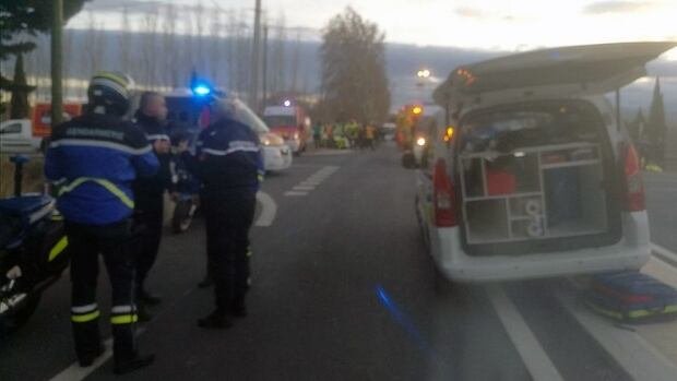 In this photo provided by France Bleu, rescue workers help after a school bus and a regional train collided in the village of Millas, southern France.