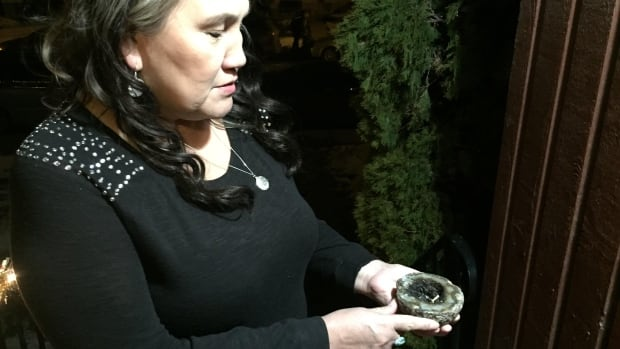 Nellie Rider stands on her front steps holding her smudge bowl. She was informed by letter last week she is not allowed to perform the ritual in her home.