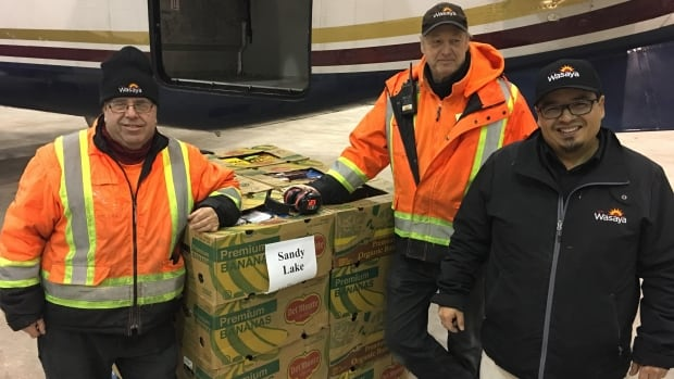 Matt Manryk, left, Alex Goriup, centre, and Waylon Gagnon, right, load food onto a plane headed to Sandy Lake.