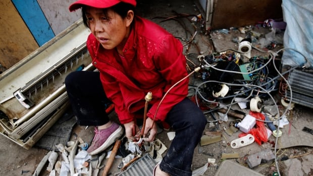 A woman dismantles a broken air-conditioning unit to sell its parts as scrap, outside a tenement house at Dongxiaokou village in Beijing in 2014.  Researchers estimate about 20 per cent of e-waste is properly recycled.