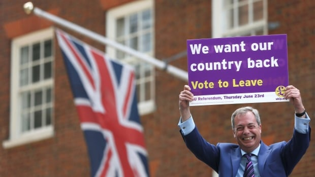 "The leader of the United Kingdom Independence Party, Nigel Farage, holds a placard in London in 2016. Questions are being raised about the data-mining companies and micro-targeted ads that were a big part of the ""Leave"" campaign's Brexit success."
