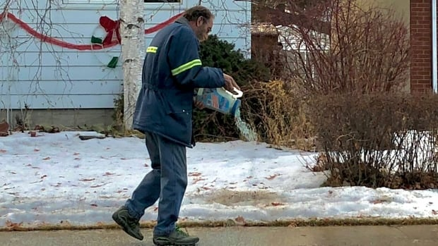 A man shakes ice melter onto a sidewalk in front of a home in the area of 37th Avenue and 111th Street on Friday morning.