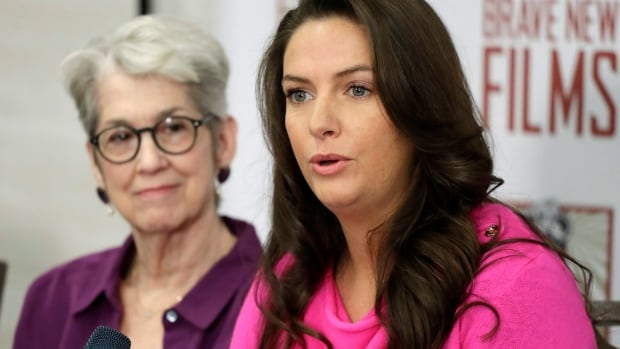 Samantha Holvey, right, speaks at a news conference on Dec. 11 in New York to discuss her accusations of sexual misconduct against U.S. President Donald Trump. Holvey says she faced a backlash when she came forward with the allegations in 2016. An expert predicts that risks associated with speaking to news media will get worse.