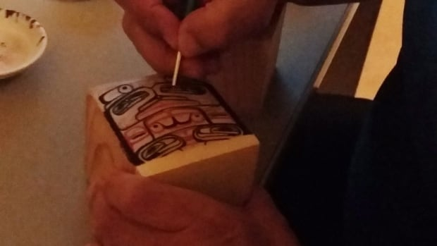Andy Wilson of the Haida First Nation paints a delicate design on a traditional Haida bentwood box. Wilson says the repatriation of many original such boxes from museum collections helped inspire and instruct a new generation of artists in his community. Other First Nations groups credit repatriation with reviving spiritual traditions that sustained their ancestors for generations.