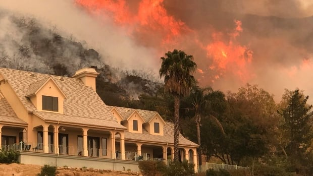 Flames from a controlled burn rise behind a home in Santa Barbara, Calif. The Thomas Fire, the third-largest in California history, has been burning in Ventura and Santa Barbara counties since it erupted Dec. 4.