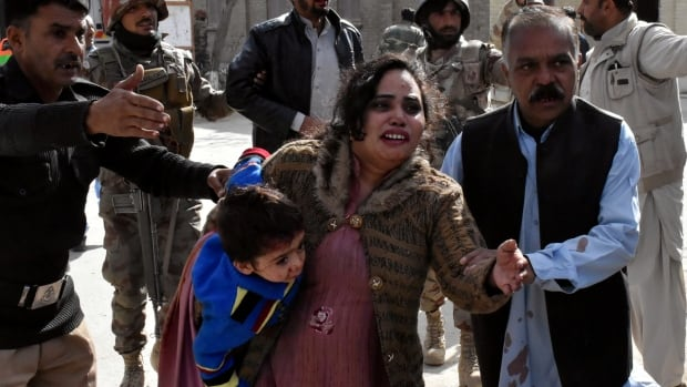 A police officer escorts a family from the Bethel Memorial Methodist Church in Quetta in Pakistan on Sunday. ISIS has claimed responsibility for the deadly attack at the church.