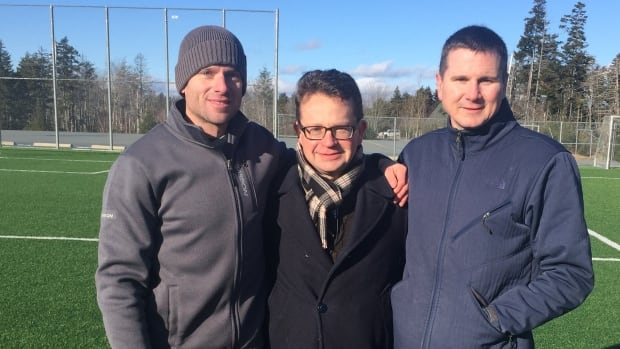 Fraser Allen, Marc Butler and Brad Thompson on the soccer field in Upper Sackville, N.S., where Butler had a heart attack a year and a half ago.