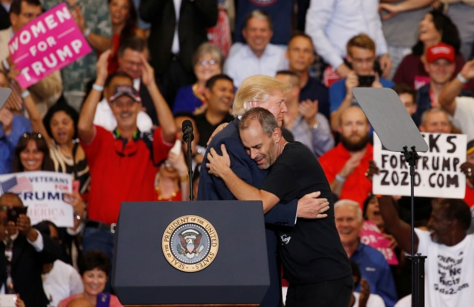 U.S. President Donald Trump hugs a supporter at rally