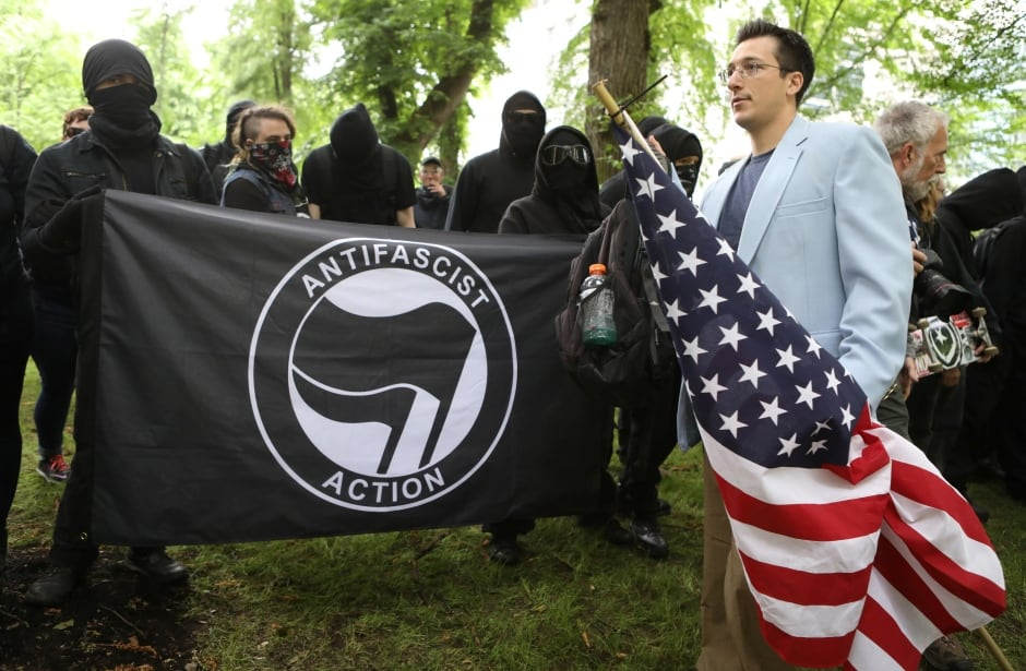 Protester walks past anti-fascist during competing demonstrations