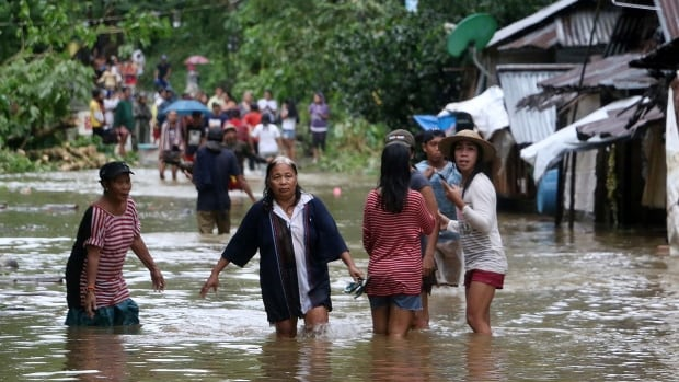 Villagers wade through a flooded street in Borongan on eastern Samar in the Philippines on Saturday. Tens of thousands were driven from their homes by floods as tropical storm Kai-Tak pounded the eastern Philippines, cutting off power and triggering landslides, officials said.