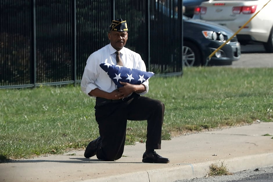 A man kneels with a folded U.S. flag as Trump's motorcade passes