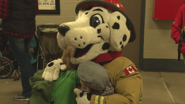 The Calgary Fire Department's mascot, Sparky, hugs attendees at the firefighter's annual Children's Christmas Party at the Stampede Corral.