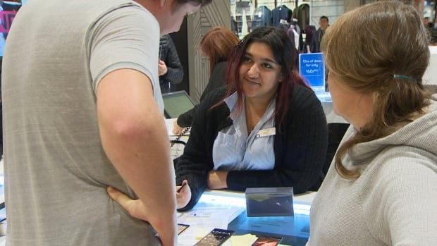 A Bell Mobility employee talks to customers at Pacific Centre Mall in downtown Vancouver. Staff at Bell say they have been overwhelmed since the company started offering a 10 GB data plan for $60 per month on Friday.