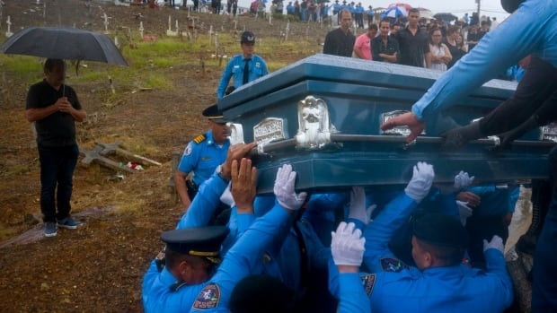 Police lift the coffin of officer Luis Angel Gonzalez Lorenzo, who was killed while trying to cross a river in Puerto Rico during Hurricane Maria. Governor Ricardo Rossello has ordered a recount of the dead from the storm after accusations that the official toll is far short of the actual number of fatalities.