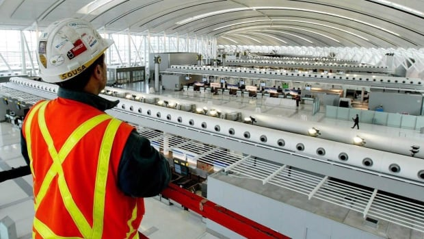 An Aecon Construction employee looks at Toronto Pearson International Airport's new Terminal 1 in this Dec. 2003 photo. The takeover of Aecon by a Chinese firm has been held up while the federal government conducts a national security review.