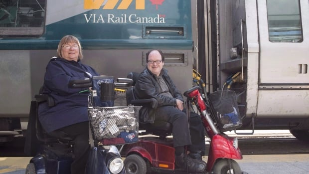 Marie Murphy, left, and Martin Anderson are pictured in front of a Via Rail train at Toronto's Union Station in May. The couple filed a complaint against Via because they could not comfortably travel together on the same train. After an 10-month dispute, the rail provider has agreed to provide two spaces for people who use scooters.