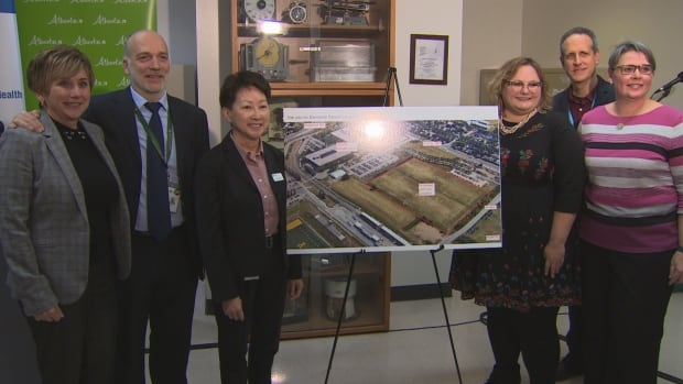 Alberta Health Minister Sarah Hoffman and Alberta Health Services staff pose in front of a picture of the Edmonton super lab location.