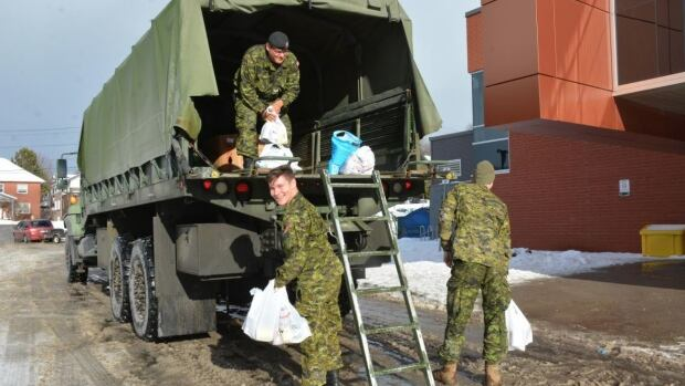 Cpl. Jason Nakogee and Cpl. Ben Hudmya, help move food donations that will go to the Sudbury Food Bank.
