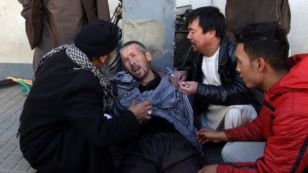A distraught man is cared for outside a hospital following a suicide attack in Kabul  on Thursday.