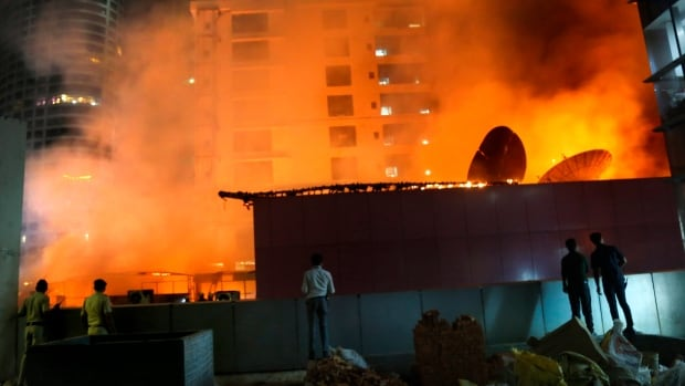 People watch as a huge fire engulfs a rooftop restaurant in Mumbai. The fire killed 14 people, police and family say.