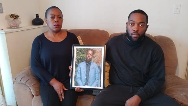 David Tshiteya Kalubi's mother Nicole Tshiteya and brother Jonathan Kalubi hold a photo of him at their Hochelaga-Maisonneuve home. David died while in police custody in early November.