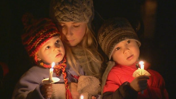 A woman and children attending the beachside vigil in memory of sisters Chloe and Aubrey Berry on Dec. 30, 2017.