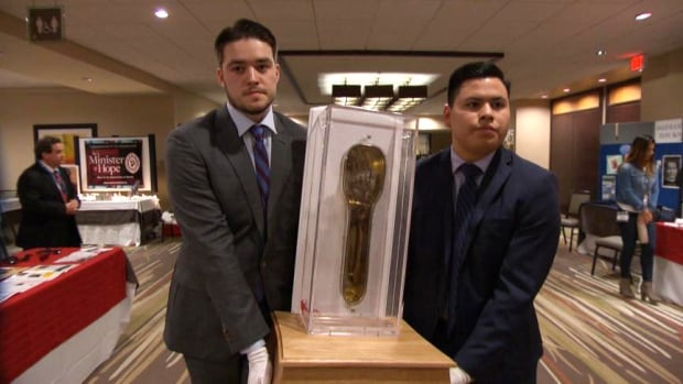 D'Arcy Murphy, left, a 19-year-old University of Ottawa student, is the guardian of the relic, responsible for carrying and travelling with the arm encased in glass.