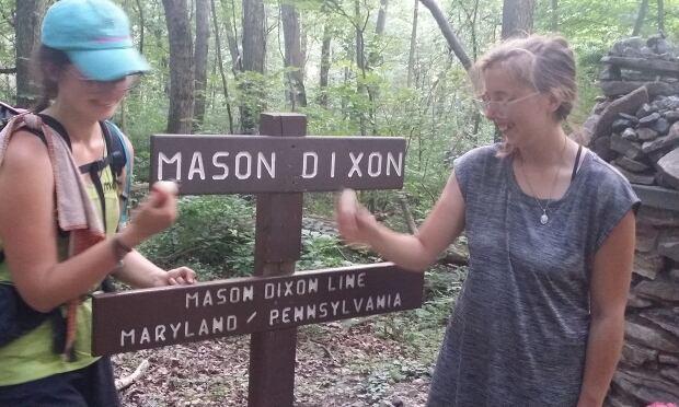 Irene MacAualy and hiking partner on Mason Dixon Line