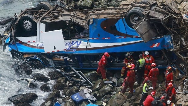 In this photo provided by the government news agency Andina, firefighters can be seen recovering bodies from a bus that fell off a cliff after it was hit by a tractor-trailer in Pasamayo, Peru, on Tuesday.
