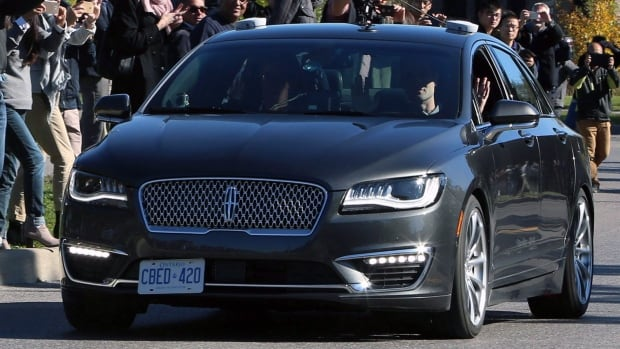 People watch as an autonomous car drives down an Ottawa street in October 2017 as the City of Ottawa and Blackberry QNX demonstrate the vehicle. BlackBerry's QNX automotive unit has been selected to provide the safety operating system for Baidu's Apollo autonomous driving system.