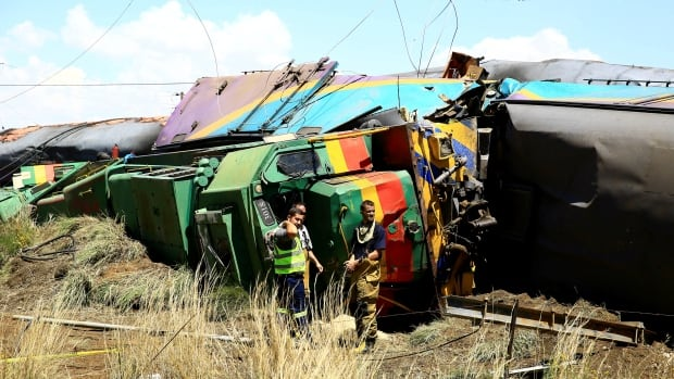 Workers stand next to wreckage after a train crash near Hennenman in Free State province, South Africa, on Jan. 4, 2018.