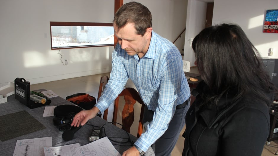 David Fancy, a theatre professor at Brock University, shows Out in the Open host Piya Chattopadhyay some of the equipment and readings he uses to gauge the electrical environment in his home.