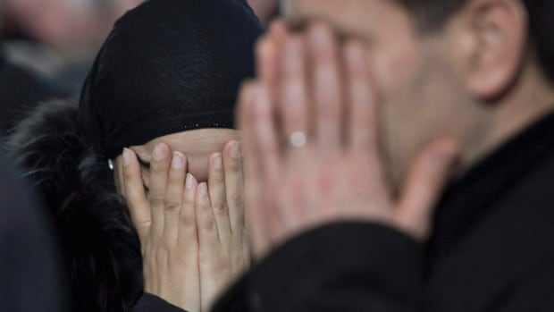 A man and a woman break down in tears during the funeral service for three of the six victims of the Quebec City mosque shooting at the Maurice Richard Arena Thursday, February 2, 2017 in Montreal.