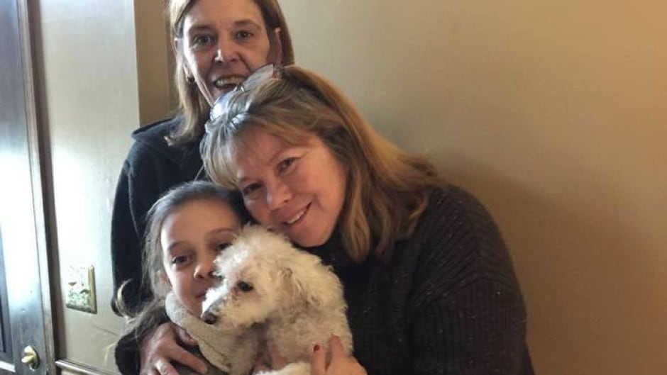 Monica Newhard, right, and her granddaughter, Helen Welch, hold their pet bichon frise, Zoey. The dog's rescuer, Christina Hartman, stands behind them.