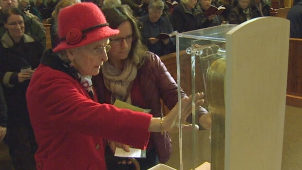 People placed prayer cards at the base of the arm's case.