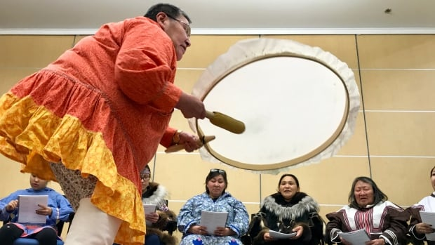 Elik Tologanak beats the drum during a weekly drum dance singing group in Cambridge Bay, Nunavut. A new drum dance song book is helping people relearn their traditional language and songs of their ancestors.