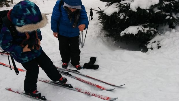 Saad and Zahra clip on their skis before heading out into the forest with their coach at Nakkertok ski club in Val-des-Monts, Que.