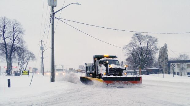 A plow moves along Victoria Street Monday morning after snow blanketed the region, making for a slow morning commute.