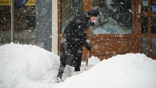 Bonnie Goodden shovels snow from the sidewalk in downtown London Monday morning, as a system bringing warmer temperatures dumped 15 cm of snow on the city by noon.