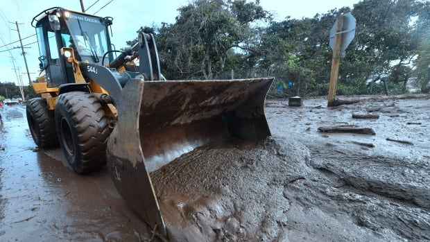 A bulldozer clears mud off the road near a flooded section of a freeway in Montecito, Calif., on Tuesday. Mudslides unleashed by a ferocious storm demolished homes in Southern California and killed more than a dozen people, police said.